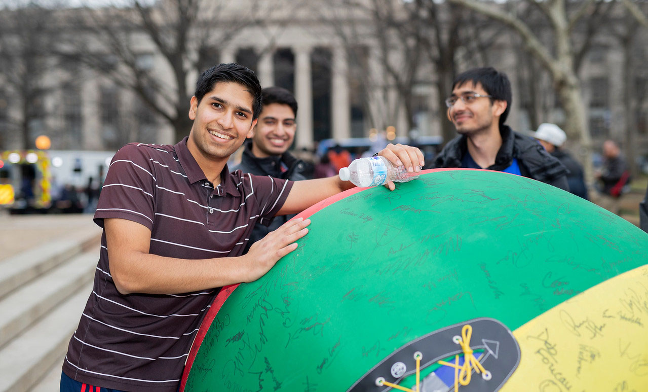 A student stands outside MIT with a giant beach ball