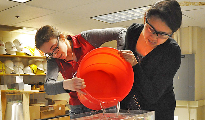 Students pour out a bucket in a lab