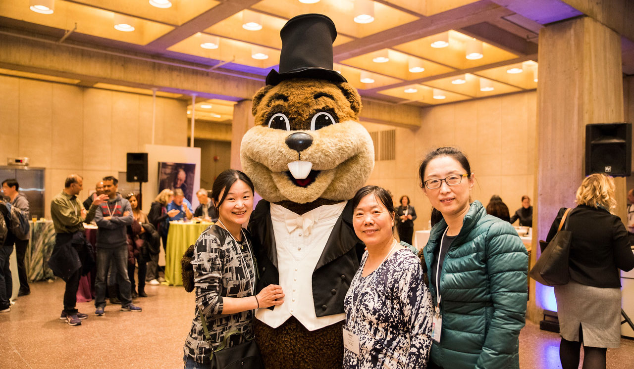 A student and two guardians with MIT's mascot, Tim the Beaver