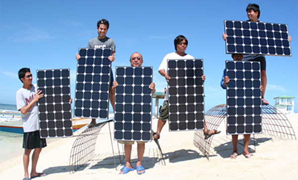 Students holding solar panels in the shape of the letters M I T