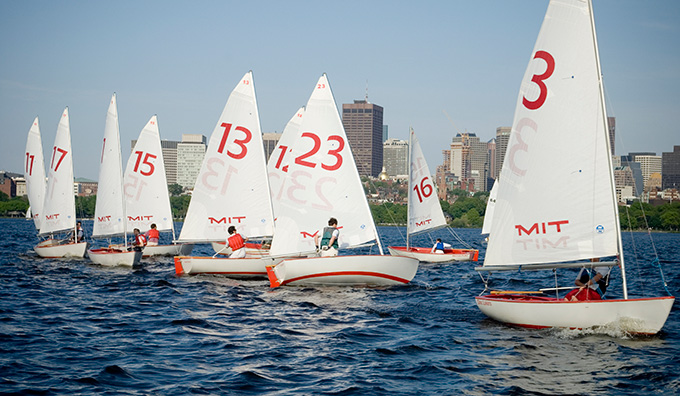 A fleet of MIT sailboats on the Charles River