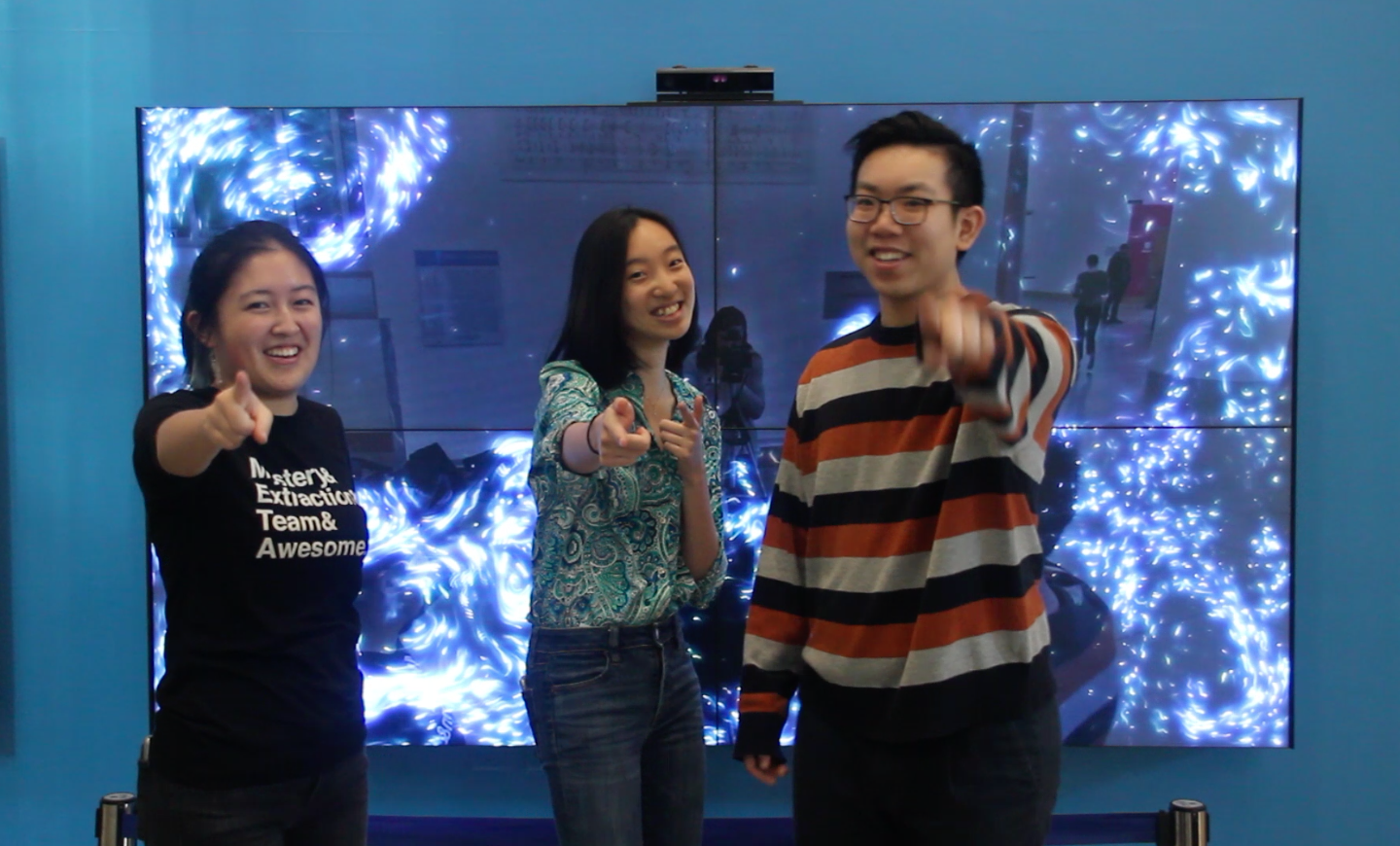 students standing in front of an interactive screen